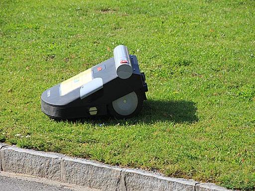 Darstellung Mähroboter auf monotoner Rasenfläche